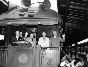 Harry S Truman waves to the crowd at train station